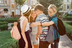 Treffen von lächelnden Freundjugendlichen in der Stadt, glückliche junge Leute, die, umarmend sich grüßen, hoch fünf gebend Freun stockbild