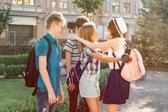 Treffen von lächelnden Freundjugendlichen in der Stadt, glückliche junge Leute, die, umarmend sich grüßen, hoch fünf gebend Freun stockbilder
