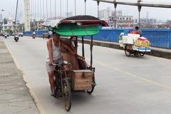 Trehjuling för arbetskraft för Rickshawpullersritt på den jingjiang bron arkivbild