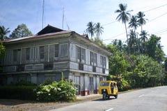 Trehjuling som passerar det traditionella Filipno huset på Camuigan ö, M Royaltyfri Fotografi