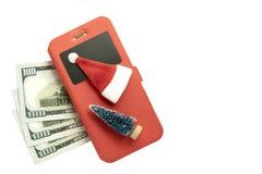 Trehundra US dollar, en smartphone i ett rött fall, en julgran och en Santa Claus souvenir och på en vit bakgrund _ royaltyfri foto