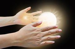 Treiben Sie Ball und elektrischen Strom in zwei Händen an Stockfotografie