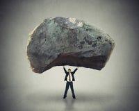 Treiben Sie Führungsfähigkeit an, den Mann anzuspornen, der herauf enormen Flussstein anhebt Lizenzfreies Stockfoto