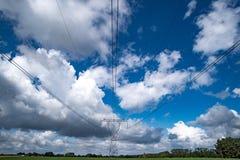 Treiben Sie Masten und Hochspannungslinien in einer landwirtschaftlichen Landschaft in Europa an Stockfotos