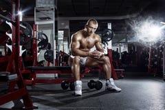 Treiben Sie sehr den athletischen Kerl an und nach Training in der Turnhalle sich entspannen Lizenzfreie Stockfotografie