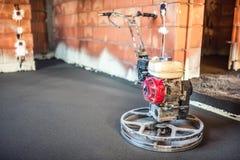 treiben Sie trowelling Werkzeug auf Betondecke an der Baustelle des neuen Hauses an Lizenzfreie Stockfotos