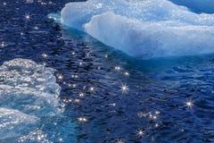 Treibende Stücke des blauen Eisbergs und der Sonne, die auf Wasser funkelt Stockfotos