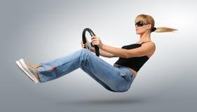 Treiber der jungen Frau in den Sonnenbrillen mit einem Rad Lizenzfreie Stockfotografie