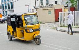 Treiber von gelben tuk tuks übt ihren Handel um die Hafenstadt aus Lizenzfreies Stockfoto