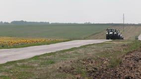 Treiberfeld des Traktorpflugbohrgeräts von Sonnenblumen stock video footage