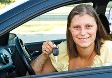 Treiberfrau, die neue Autotasten zeigend lächelt Stockfotografie