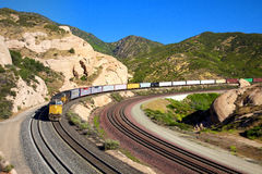 Treight train passing through the curve. A train scene, pulling several carriages passing through the curve Stock Photo