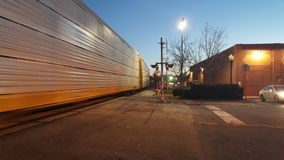 Trein die afgelopen spoorweg bewegen die bij schemer 1 kruisen Stock Foto's