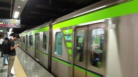 Trein die bij een platform aankomen van de metropost terwijl de forenzen in lijn, Tokyo, Japan wachten stock footage