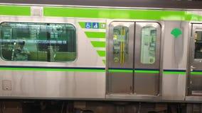 Trein die bij een platform aankomen van de metropost terwijl de forenzen in lijn, Tokyo, Japan wachten stock videobeelden