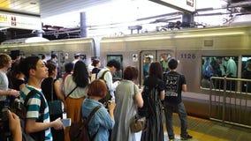 Trein die bij een platform aankomen van de metropost terwijl de forenzen in lijn, Tokyo, Japan wachten stock video