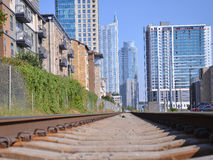 Trein die met de stad in op de Achtergrond overgaan Stock Fotografie