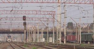 Trein die met veel dradenkabels en torens met hoog voltage op station naderbij komen stock footage