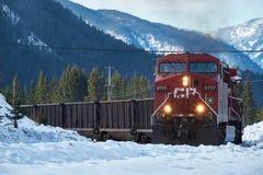 Trein die om de kromming met Canadese Rotsachtige Bergen in de winter komen Royalty-vrije Stock Foto's