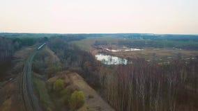 Trein die tot een afstand bij de dubbele lijnspoorweg overgaan stock footage