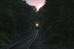 Trein die uit het plaatsen van zon komt Stock Afbeeldingen