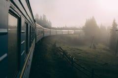 Trein die zich in de bergen in mist bewegen Karpatische bergen Mening van Venster stock fotografie