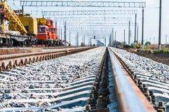 Trein met speciaal spoormateriaal bij reparaties stock foto's