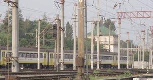 Trein naderbij komende post met elektrische torenspartijen met hoog voltage van kabelsdraden en van treinverkeerlichten mensen di stock footage