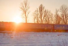 Trein op de achtergrond van de zonsondergangwinter Stock Afbeelding