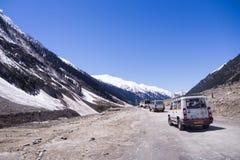 Trein van auto's op avonturenweg onder sneeuwberg Royalty-vrije Stock Afbeeldingen