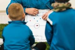 Treinador Coaching Children do futebol da juventude Táticas de escuta dos treinadores dos jogadores de futebol dos meninos e conv fotografia de stock royalty free