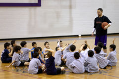Treinador de beisebol com os estudantes no Gym imagem de stock