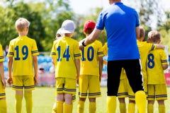 Treinador de futebol da juventude que fala à equipe de futebol das crianças Treinamento dos esportes fotos de stock