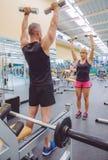 Treinador do homem que treina à mulher com pesos Fotos de Stock