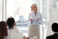Treinador fêmea maduro do negócio que fala na equipe que encontra o treinamento s foto de stock royalty free