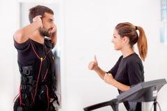 Treinador fêmea que dá a homem ems o eletro exerci muscular da estimulação foto de stock