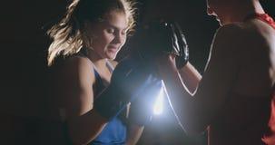 Treinador kickboxing do atleta da mulher de Kickboxer que treina os amigos fêmeas da aptidão que encaixotam a apreciação de perfu filme