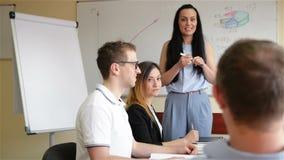 Treinador Mentor Leader Speaking do professor fêmea que ensina a estudantes diversos do pessoal internos na reunião do escritório video estoque