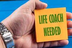 Treinador Needed Text Concept da vida com o de papel de notas pegajoso na mão fotografia de stock royalty free