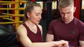 Treinador pessoal muscular que escreve na prancheta e que discute o plano de formação à jovem mulher no gym da formação transvers vídeos de arquivo