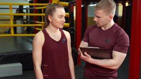 Treinador pessoal muscular que escreve na prancheta e que fala à jovem mulher no gym da formação transversal filme