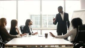 Treinador preto que dá a apresentação para empresários no escritório com flipchart filme