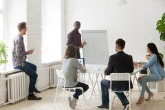Treinador preto que fala sobre estratégias empresariais ao trabalho diverso GR imagens de stock