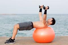 Treinamento abdominal da bola no lado de mar Fotografia de Stock