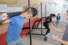 Treinamento adolescente com pesos no clube do gym com treinador fotos de stock