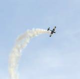 Treinamento Aerobatic de Jurgis Kairys do piloto do avião no céu da cidade Avião colorido com fumo do traço, airbandits, aeroshow Imagem de Stock Royalty Free
