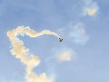 Treinamento Aerobatic de Jurgis Kairys do piloto do avião no céu da cidade Avião colorido com fumo do traço, airbandits, aeroshow Fotografia de Stock Royalty Free