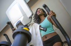 Treinamento americano da mulher do africano negro atrativo e feliz no sorriso do clube de aptidão alegre e suado durante a máquin imagem de stock royalty free