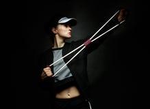 Treinamento apto da mulher com a faixa da resistência contra o fundo preto imagens de stock royalty free