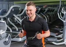 Treinamento apto de sorriso considerável do homem na máquina moderna da fileira no gym Imagens de Stock Royalty Free